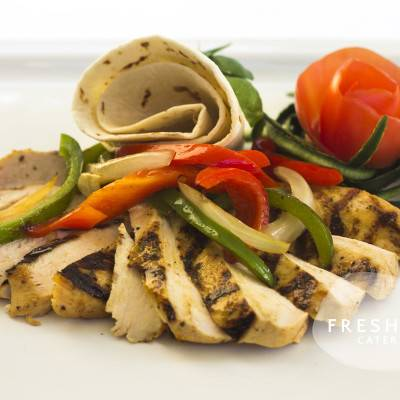 Grilled chicken Fajitas with bell peppers and onions. Served with flour tortillas
