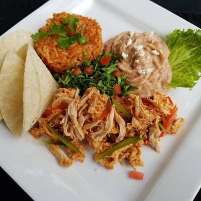 Shredded chicken tacos with lettuce and tomato. Served with beans and rice