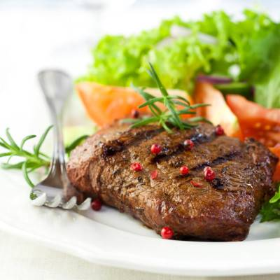 Steak topped with rosemary and garden salad on side