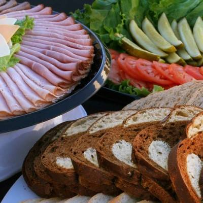 Sandwich builder platter with an assortment of meats, cheeses, veggies, and breads