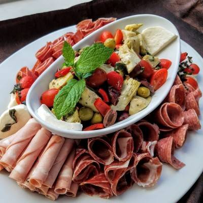 Antipasto Platter of assorted cured meats and cheeses with artichokes and olives on the side