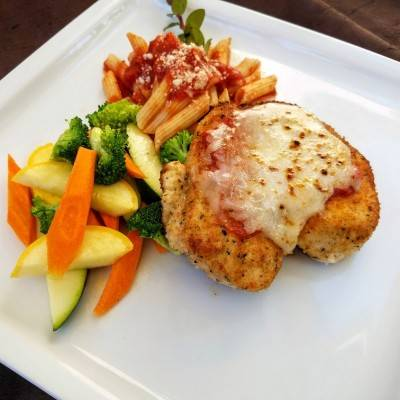 A classic chicken parmigiana with penne pasta and tomato sauce and a side of veggies