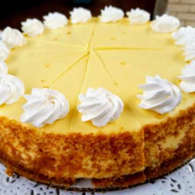 sliced plain cheese cake topped with whip cream