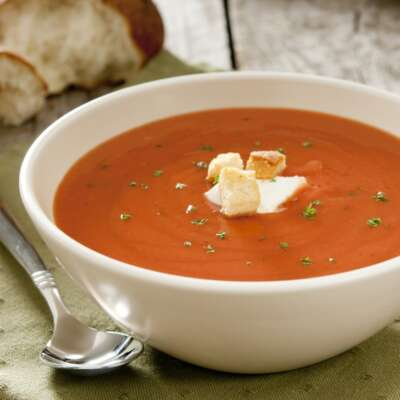 Freshella Catering cream of tomato soup on a white bowl, spoon next to it