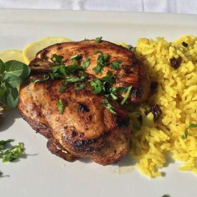 Sauteed grilled chicken with spices and lemon zest with side of rice with raisins