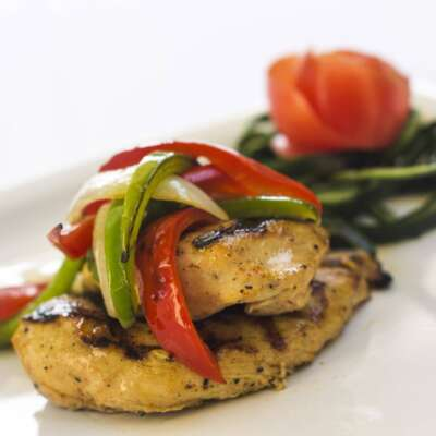 Corporate catering menu item of grilled chicken breast topped with bell peppers and onions