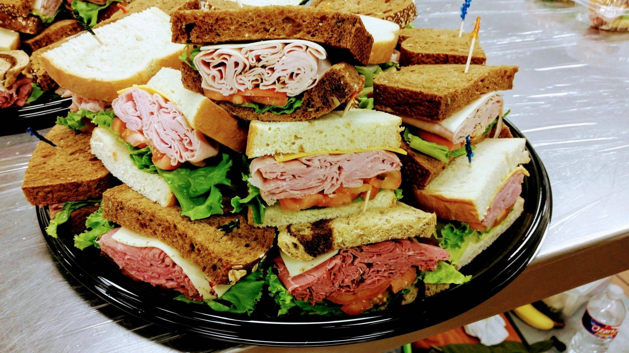 Platter filled with sandwiches with a variety of meats, cheeses, and breads.