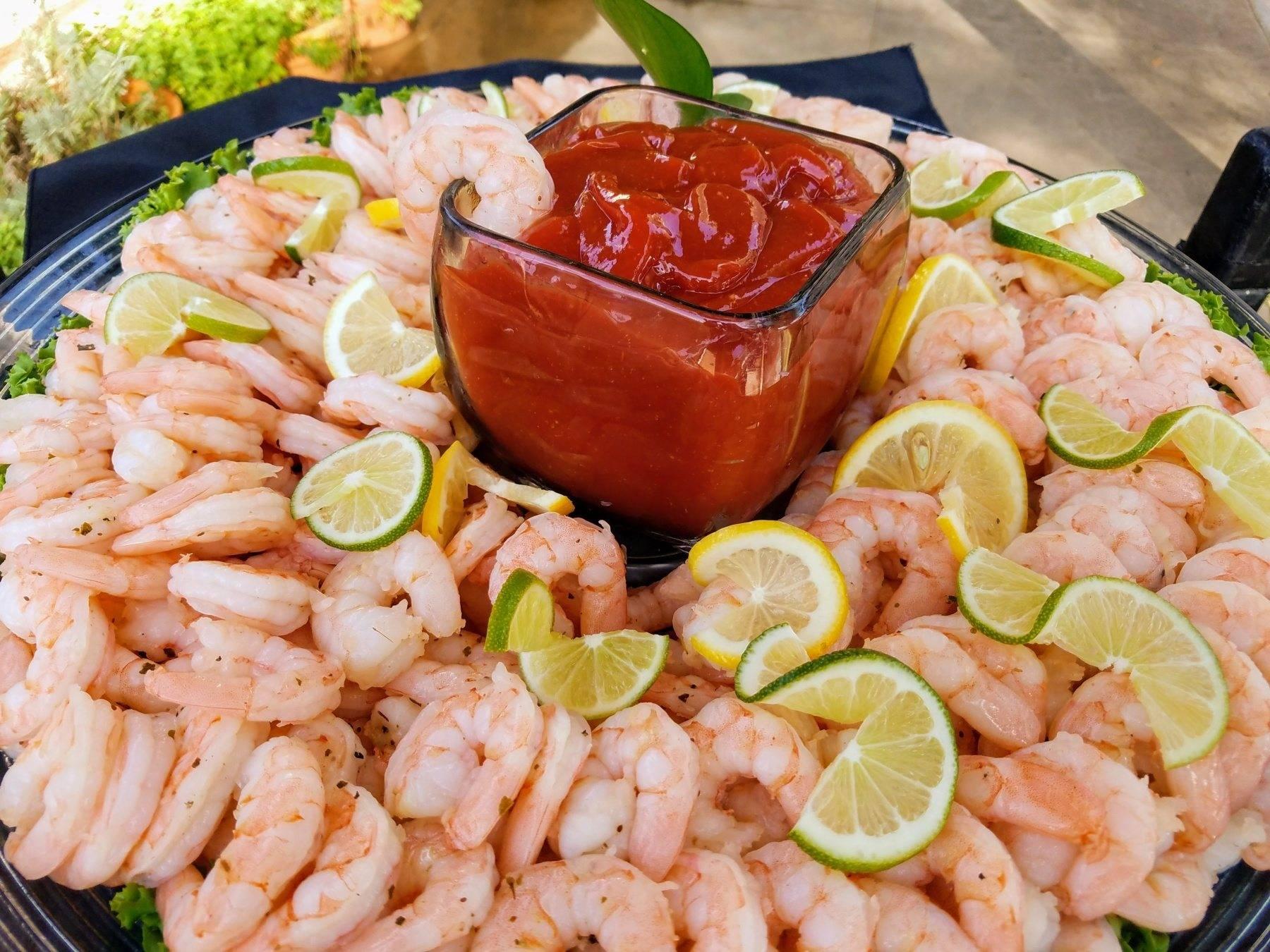 poached shrimp arranged on black platter garnished with lemon and lime wedges, side of cocktail sauce