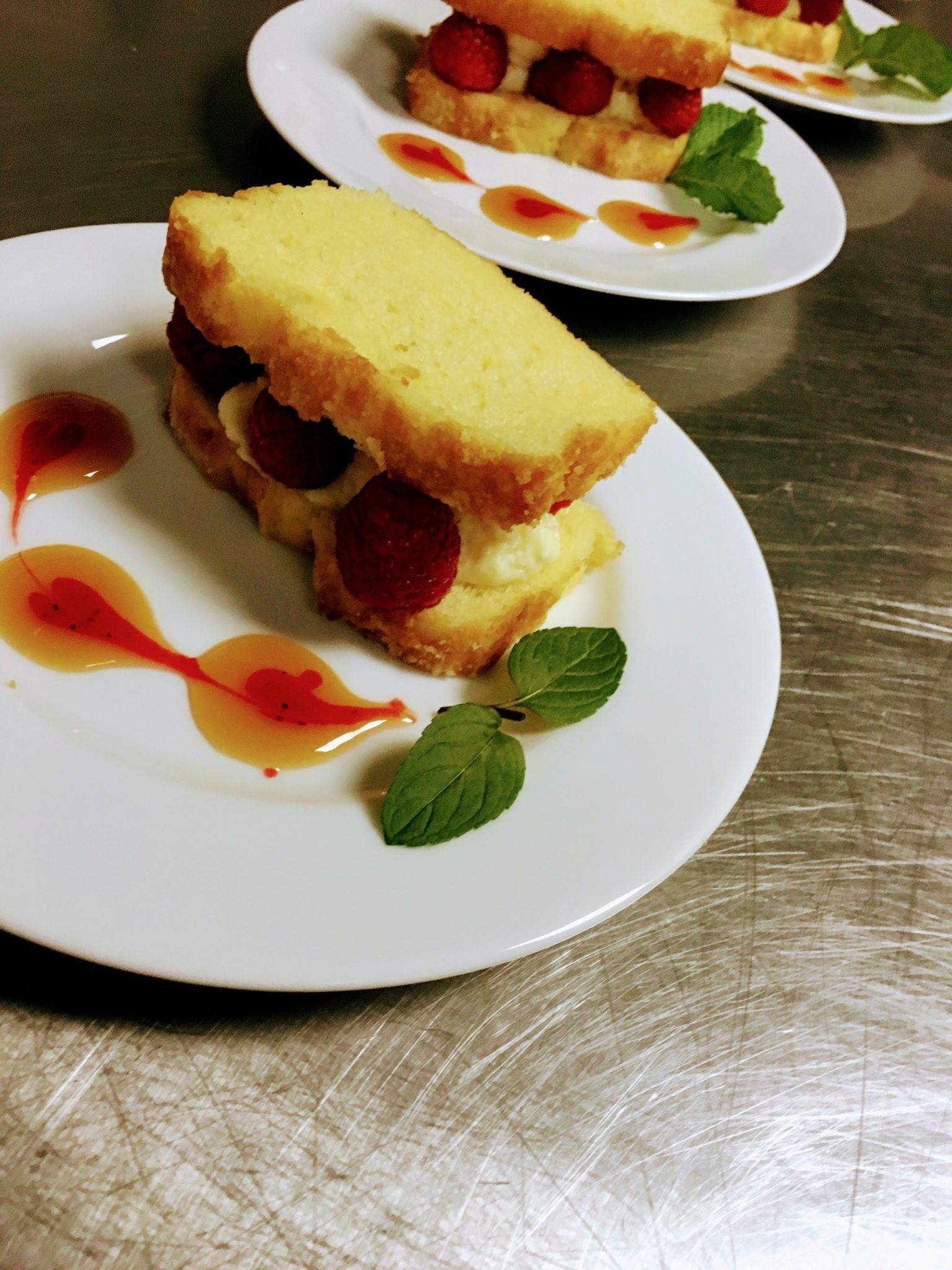 Two pieces of shortcake with berries and cream between them