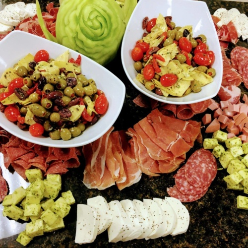 Party catering platter of Cheese, Aged Sliced Italian Meats, artichokes, olives, peppers, on marble slab display