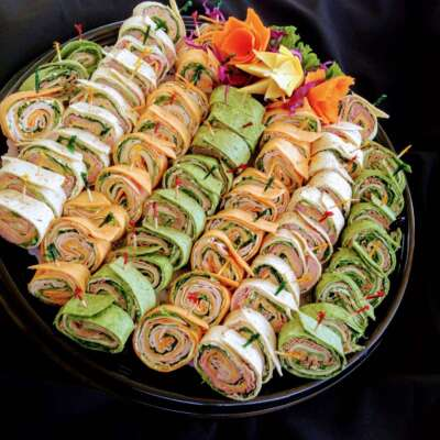catering tortilla pinwheel roll ups arranged on a black platter