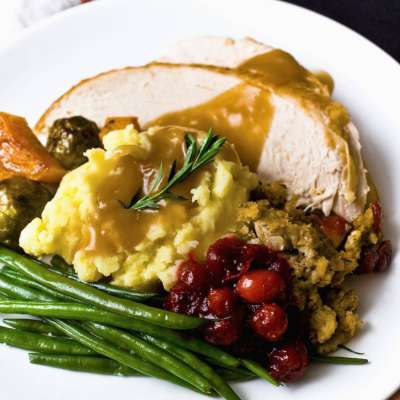 catering meal of sliced turkey breast with brown gravy, mashed potatoes, green beans, stuffing and cranberry sauce