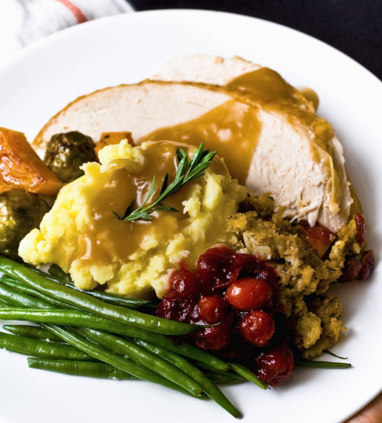 Sliced Roasted Turkey Breast, Brown Gravy, Mashed Potatoes, Green Beans, Stuffing, Cranberry Sauce, Green Beans