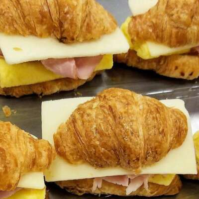mini croissant breakfast sandwiches filled with egg patty, sliced ham and swiss cheese