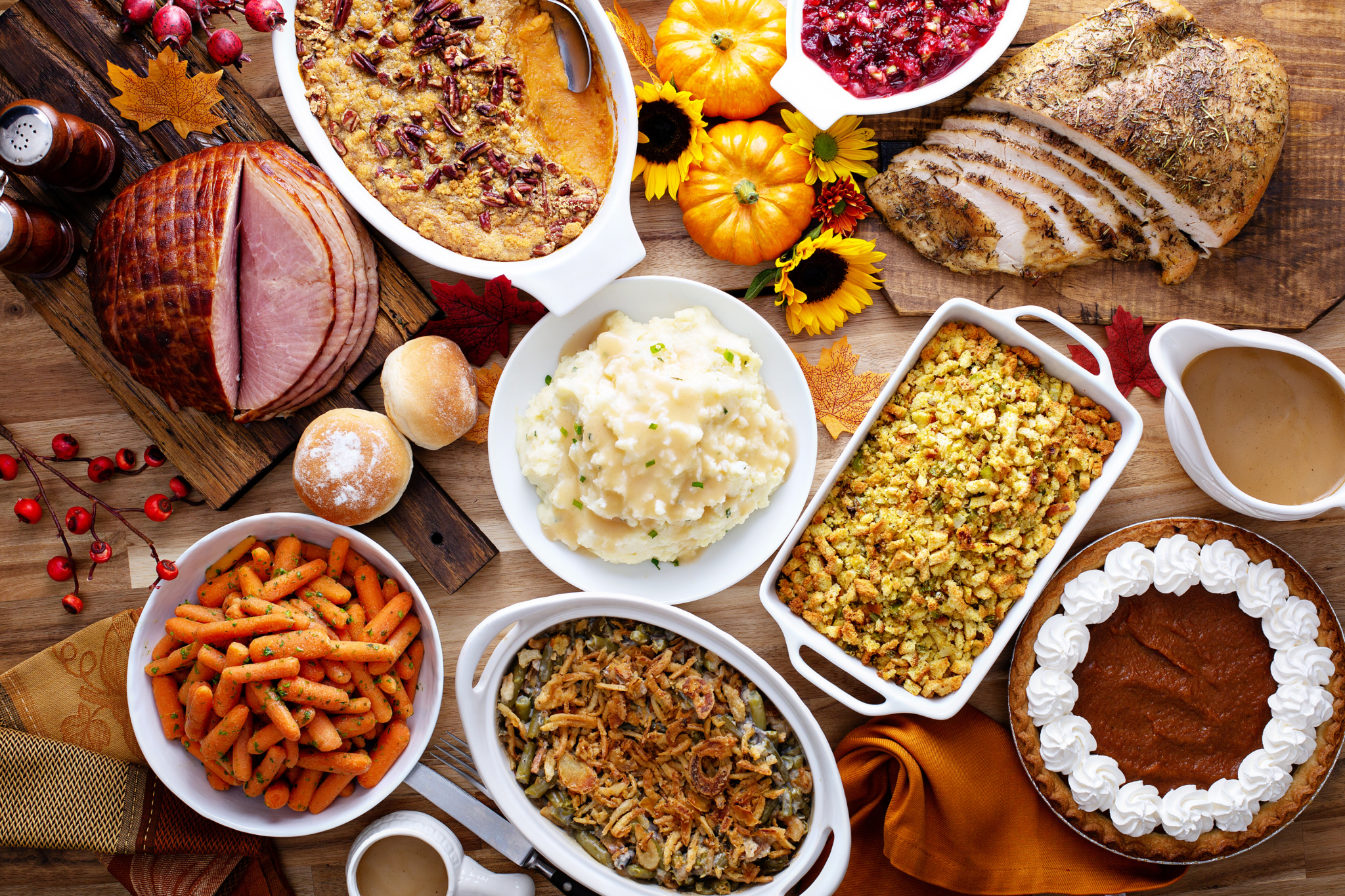 View from above of a holiday table display. Carrots, green bean casserole, stuffing, pumpkin pie, mashed potatoes, sliced turkey and ham and cranberry sauce