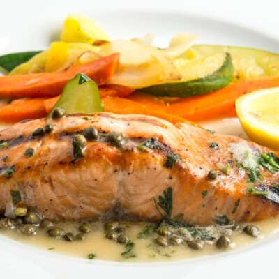 Showing Lemon Caper salmon from Freshella Catering accompanied by mixed grilled veggies