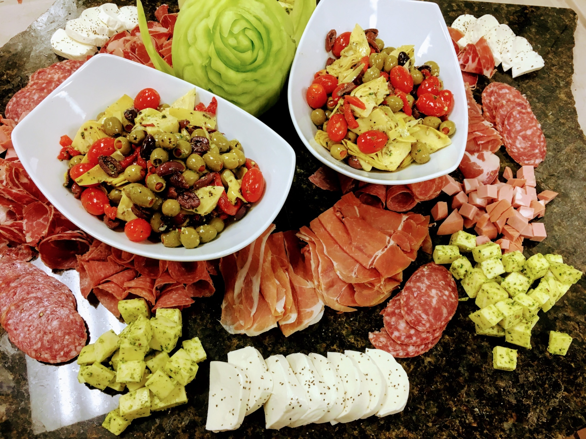 Party catering display of assorted cured meats with olives and different cheeses on a marble stone