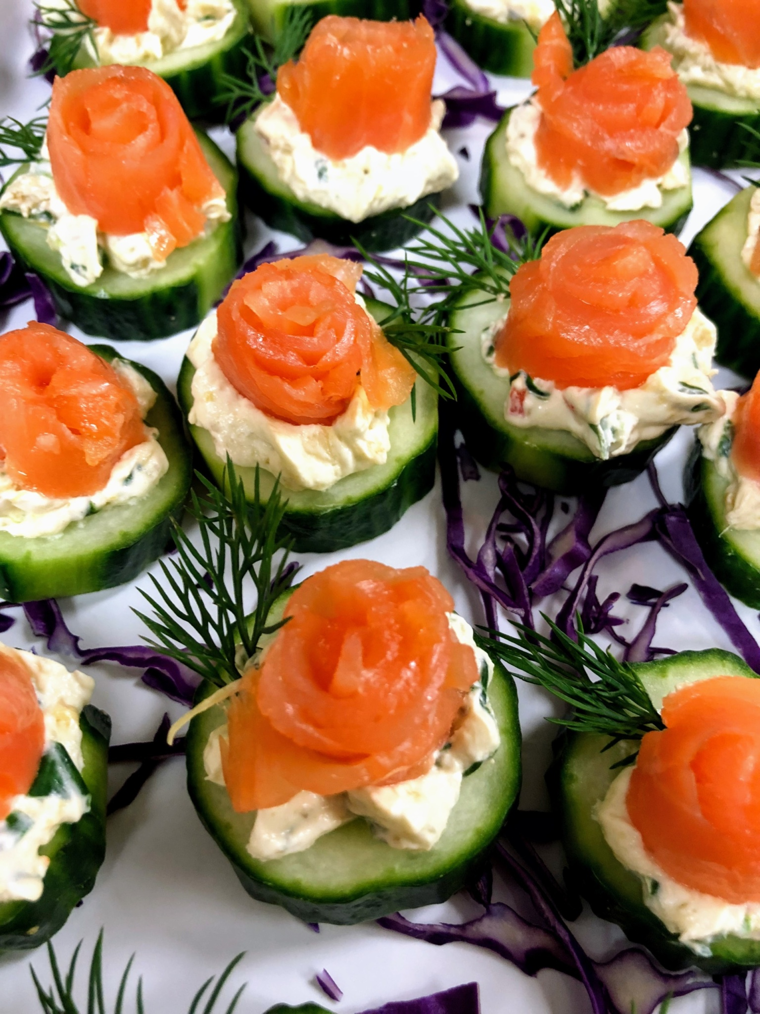 A display of beautifully arranged Salmon Rosettes on cucumber on a white china platter